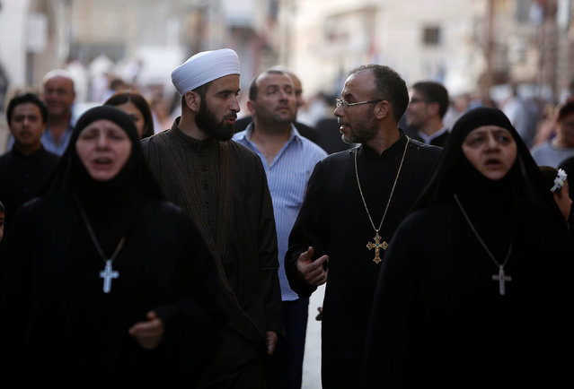 A Muslim Sheikh (C-L) chats with a Christian priest while marching with nuns and faithful along a street during Saidnaya Festival, near Damascus, Syria September 7, 2016. (Photo by Omar Sanadiki/Reuters)