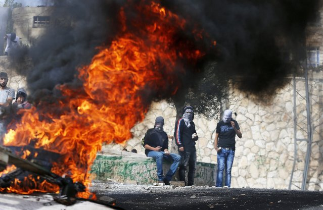 Stone-throwing Palestinian youths stand next to a fire during clashes with Israeli police in Sur Baher, a village in the suburbs of Arab east Jerusalem October 7, 2015. (Photo by Ammar Awad/Reuters)
