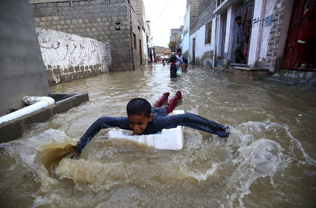 Children play in rain water after heavy rains in Karachi, Pakistan, 26 July 2020. (Photo by Shahzaib Akber/EPA/EFE)