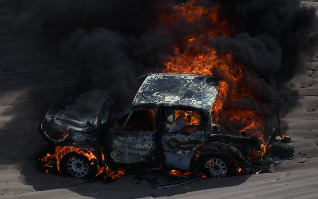 The car driven by Argentinian driver Alicia Reina and co- driver Carlos Pelayo catches fire during Stage 3 of the Dakar 2018 between Pisco and San Juan de Marcona, Peru, on January 8, 2018. The drivers escaped uninjured. (Photo by Franck Fife/AFP Photo)