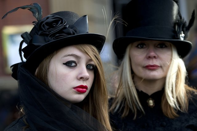 "Women dressed in gothic costumes pose for pictures during the biannual ""Whitby Goth Weekend"" (WGW) festival in Whitby, Northern England, on November 2, 2014. (Photo by Oli Scarff/AFP Photo)"