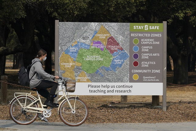 A bicyclist rides past a sign showing restricted zones around the Stanford University campus in Stanford, Calif., Wednesday, September 2, 2020. With the coronavirus spreading through colleges at alarming rates, universities are scrambling to find quarantine locations in dormitory buildings and off-campus properties to isolate the thousands of students who have caught COVID-19 or been exposed to it. (Photo by Jeff Chiu/AP Photo)