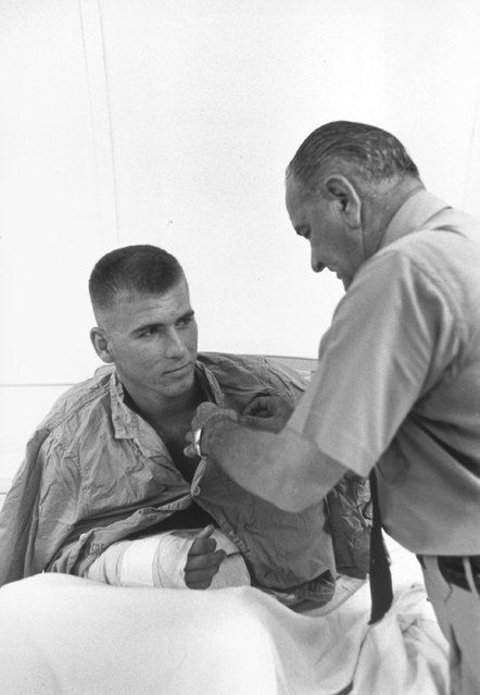 """President Lyndon Johnson awards a medal to a wounded U.S. serviceman in Cam Rahn Bay, South Vietnam, October 26, 1966"". (Photo by Yoichi Okamoto)"
