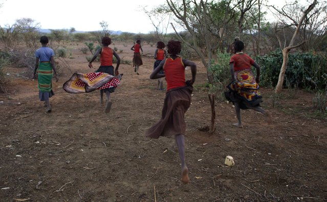 Pokot girls run from their hut and make their way to a place where they will take off their clothes and wash during their circumcision ceremony in a village about 80 kilometres from the town of Marigat in Baringo County, October 16, 2014. (Photo by Siegfried Modola/Reuters)