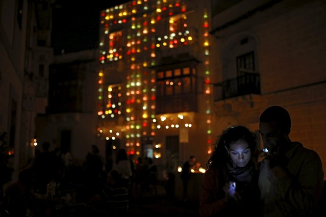 "Visitors check photos on a smartphone during the activity ""Birgu by Candlelight"" in the medieval city of Birgu, also known as Vittoriosa, outside Valletta, Malta, October 10, 2015. (Photo by Darrin Zammit Lupi/Reuters)"