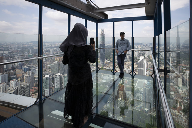 Tourists pose for photos at the Skybox at Kuala Lumpur Tower in Kuala Lumpur, Malaysia, Wednesday, July 1, 2020. Malaysia entered the Recovery Movement Control Order (RMCO) after three months of coronavirus restrictions. (Photo by Vincent Thian/AP Photo)
