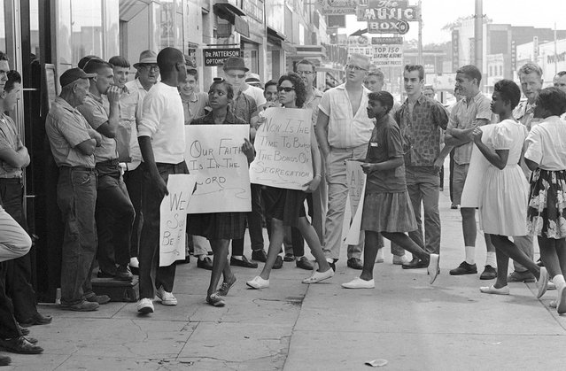 A picketer in front of a Gadsden, Alabama, drugstore turns to answer a heckler during a demonstration, on June 10, 1963. About two dozen black youths picketed several stores and two theaters. There were no arrests and no violence. (Photo by AP Photo)