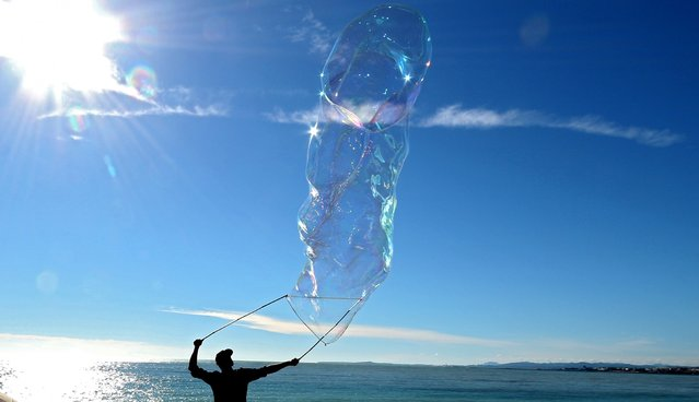 A man makes giants soap bubbles on the Promenade des Anglais in Nice, southeastern France, Sunday, November 16, 2014. Temperatures in the area rose to 19 degrees Celsius (66 Fahrenheit). (Photo by Lionel Cironneau/AP Photo)