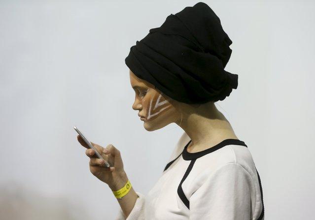 A model checks her mobile phone as she waits backstage at Ukrainian Fashion Week in Kiev, October 17, 2015. (Photo by Valentyn Ogirenko/Reuters)