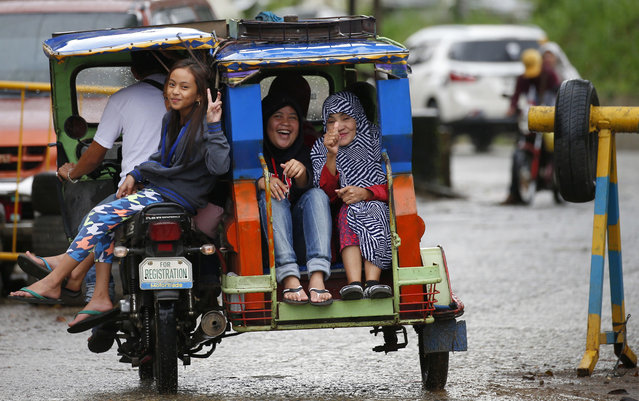Residents recently returning to their area cleared by government troops react as they ride a tricycle a day after President Rodrigo Duterte declared the liberation of Marawi city in southern Philippines Wednesday, October 18, 2017. Sporadic explosions continue Wednesday as Philippine soldiers fought to gain control of the last pocket of Marawi controlled by Islamic militants. (Photo by Bullit Marquez/AP Photo)