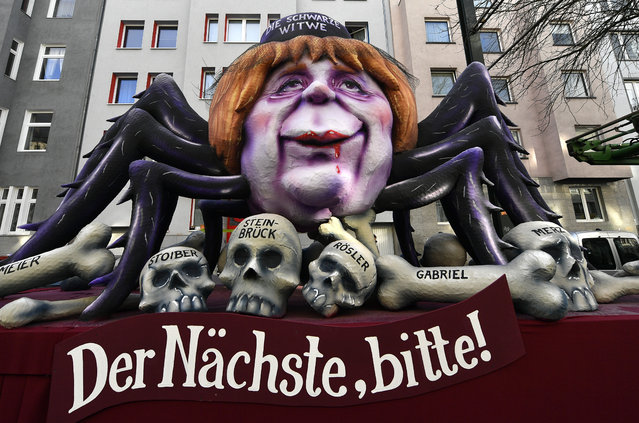 """A float depicts German Chancellor Angela Merkel as black widow with the skulls of former opponents in front and the writing """"Next one please"""" during the traditional Rose Monday parade in Duesseldorf, Germany, Shrove Monday, February 12, 2018. (Photo by Martin Meissner/AP Photo)"""