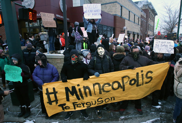 Demonstrators gather, Tuesday, November 25, 2014, outside the  Minneapolis Police Department's Third Precinct to protest Monday's announcement that a grand jury has decided not to indict Ferguson, Mo., police officer Darren Wilson in the shooting death of unarmed, black 18-year-old Michael Brown. (Photo by Jim Mone/AP Photo)