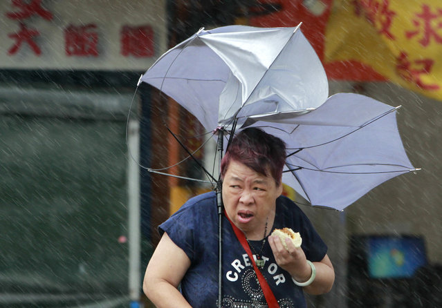 A woman eats and struggles with her umbrella against powerful gusts of wind generated by typhoon Megi across the the island in Taipei, Taiwan, Tuesday, September 27, 2016. Schools and offices have been closed on Taiwan and people in dangerous areas have been evacuated as a large typhoon with 162 kilometers (100 miles) per-hour winds approaches the island. (Photo by Chiang Ying-ying/AP Photo)