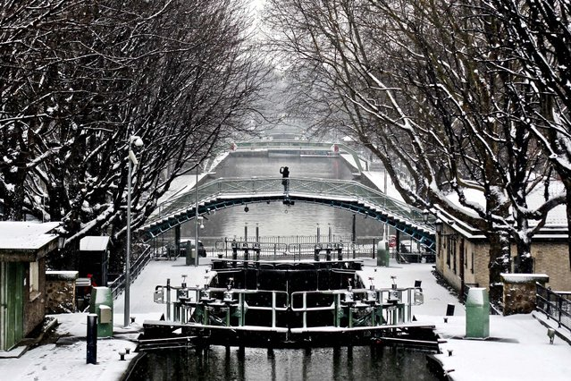 A person takes a photo from a bridge, at the canal St Martin, in Paris, on March 12, 2013. Hundreds of flights out of Western Europe have been cancelled, no trains running under the English Channel, and Belgium's prince is stuck at home, all because of a sudden dump of oddly late snowfall on Western Europe. (Photo by Thibault Camus/Associated Press)