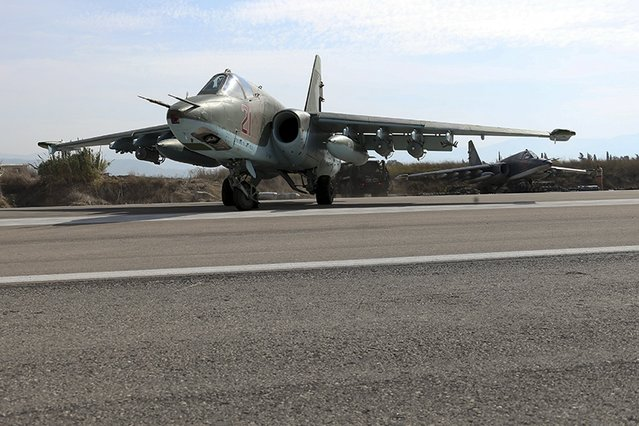 Sukhoi Su-25 fighter jets are seen on the tarmac at the Hmeymim air base near Latakia, Syria, in this handout photograph released by Russia's Defence Ministry October 22, 2015. (Photo by Reuters/Ministry of Defence of the Russian Federation)