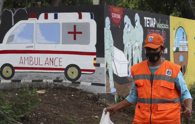 A worker wearing a face mask as a precaution against the coronavirus walks past a coronavirus-themed mural in Jakarta, Indonesia, Monday, October 5, 2020. (Photo by Achmad Ibrahim/AP Photo)