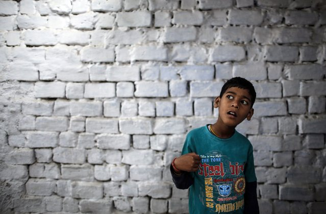 Eight-year-old Abhi, who suffers from mental and physical disabilities, plays outside his house at a slum in Bhopal November 15, 2014. Abhi receives treatment at a rehabilitation centre supported by Bhopal Medical Appeal which only treats families they believe have been affected by the Union Carbide gas leak 30 years ago. (Photo by Danish Siddiqui/Reuters)