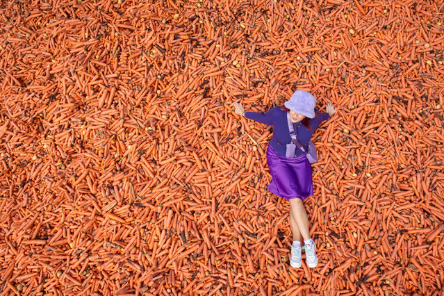 """Student Lauren Gallagher with the art installation """"Grounding"""" by Rafael Perez Evans, which is made up of 29 tonnes of unwanted carrots ouside the Ben Pimlott building at Goldsmiths College, London on October 1, 2020. (Photo by Dominic Lipinski/PA Images via Getty Images)"""
