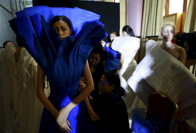 Staff help a model wearing a dress at the backstage before the fashion show of ECHO CHEN Collection at China Fashion Week S/S 2016 in Beijing, October 26, 2015. (Photo by Kim Kyung-Hoon/Reuters)