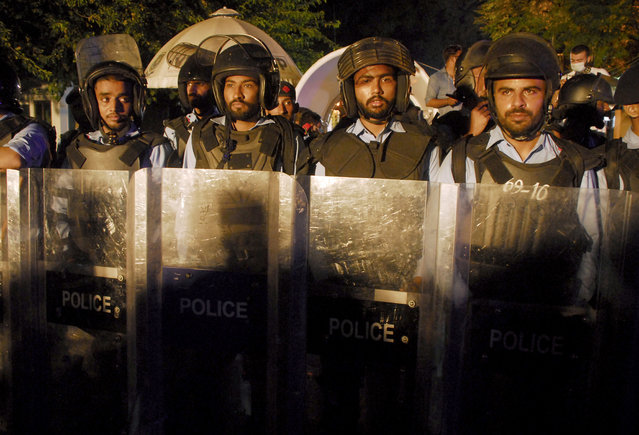 Police officers stand guard near Indian High Commission, while members of the Pakistani Hindu community stage a join a sit-in protest in Islamabad, Pakistan, Thursday, September 24, 2020. Pakistan's minority Hindus rallied late on Thursday in Islamabad to protest the deaths of 11 members of a Hindu migrant family who died in India last month under mysterious circumstances. The protesters accuse India's secret service of poisoning the victims, who were found dead at a farmhouse in India's Jodhpur district in Rajasthan state. (Photo by A.M. Chaudary/AP Photo)