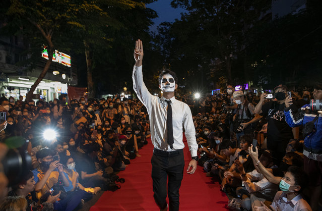 """Pro-democracy protesters perform on a mock """"red carpet"""" fashion show billed as a counterpoint to a fashion show being held by one of the monarchy's princesses nearby in Bangkok, Thailand, Thursday, October 29, 2020. The protesters continued to gather Thursday, led by their three main demands of Prime Minister Prayuth Chan-ocha's resignation, changes to a constitution that was drafted under military rule and reforms to the constitutional monarchy. (Photo by Gemunu Amarasinghe/AP Photo)"""