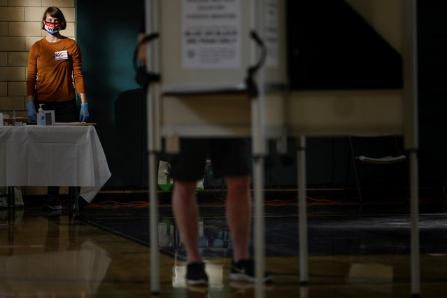 Ballot clerk Chris Biles looks on through a plexiglass barrier while wearing personal protective equipment at the School Without Walls at Francis-Stevens voting station in Washington, U.S., on October 28, 2020. (Photo by Tom Brenner/Reuters)