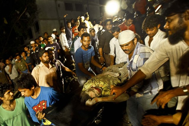 Rescue workers carry the body of a man near the site of a building collapse in Thane, Mumbai, India, killing 35 people and injuring more than 50, on April 4, 2013.  (Photo by Rafiq Maqbool/Associated Press)