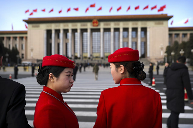 Hospitality staff members stand outside the Great Hall of the People as they wait for delegates to leave after the closing session of the Chinese People's Political Consultative Conference (CPPCC) in Beijing, Thursday, March 15, 2018. (Photo by Mark Schiefelbein/AP Photo)