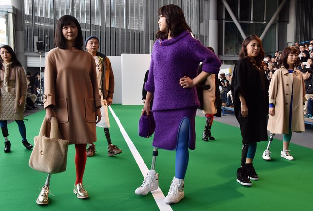 """Japanese athletes with physical disabilities display creations of """"Theater Products"""" designed by designers Akira Takeuchi and Miwa Fujiwara during a fashion show at the National Museum of Emerging Science and Innovation in Tokyo on December 7, 2014. Fifteen athletes including Paralympians showed off the latest outfits at an event as a part of the Disabled Week. (Photo by Yoshikazu Tsuno/AFP Photo)"""