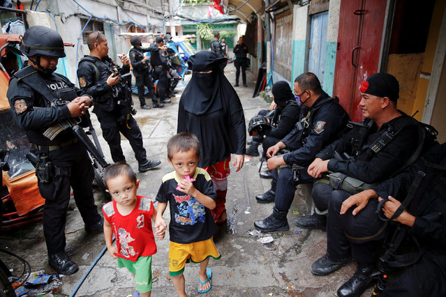 Members of the police SWAT team rest as residents walk by during a drug raid, in Manila, Philippines, October 7, 2016. (Photo by Damir Sagolj/Reuters)