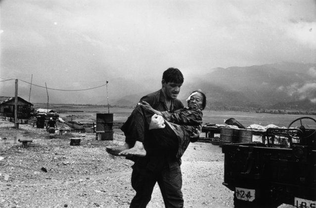 A US soldier carrying a wounded refugee to safety during the war in Vietnam, 1968. (Photo by Terry Fincher/Daily Express/Hulton Archive/Getty Images)