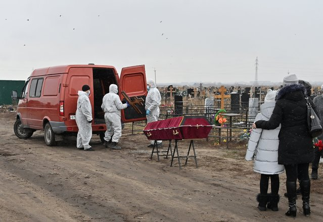 Grave diggers wearing personal protective equipment (PPE) prepare to bury a person, who presumably died of the coronavirus disease (COVID-19), at a cemetery in Omsk, Russia on November 3, 2020. (Photo by Alexey Malgavko/Reuters)