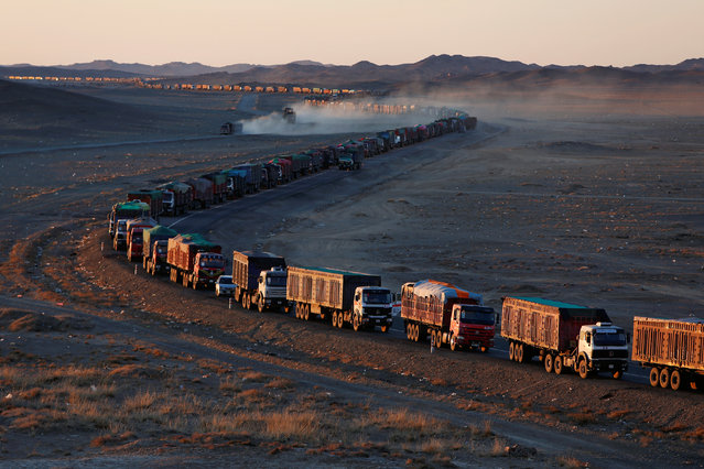 Thousands of heavy-duty trucks loaded with coal are lined up for up to 130 kilometres from the Mongolia-China border on a sole road in the Gobi desert, Mongolia, October 29, 2017. The journey can take more than a week. (Photo by Bazarsukh Rentsendorj/Reuters)