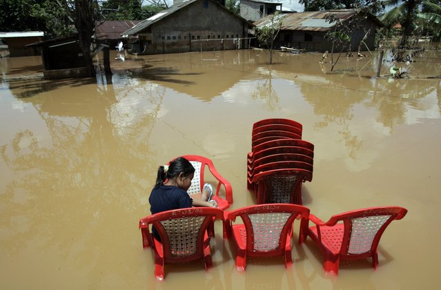 A resident sits on a plastic chair in a flooded residential area in Jakarta in this March 15, 2007 file photo. (Photo by Reuters/Supri)