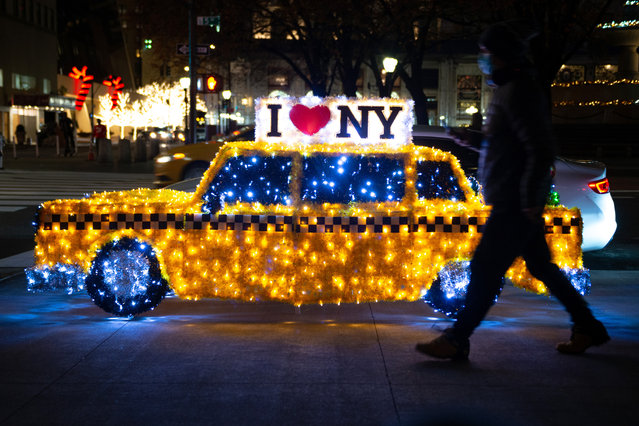 "A man wearing a mask walks past the ""Christmas Cab"" sculpture displayed along Fifth Avenue on December 02, 2020 in New York City. The annual Holiday Sculptures display is organized by the Fifth Avenue Association and consist of 10 sculptures that runs from 50th Street to 59th Street. (Photo by Alexi Rosenfeld/Getty Images)"