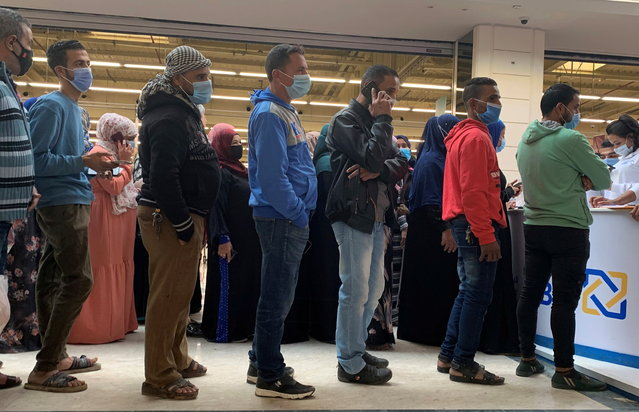 People wearing protective face masks wait in line in front of Al Ahli Bank of Kuwait (ABK) stand inside a Carrefour hypermarket ahead of Black Friday, amid the coronavirus disease (COVID-19) pandemic in the Cairo suburb of Maadi, Egypt on November 26, 2020. (Photo by Amr Abdallah Dalsh/Reuters)