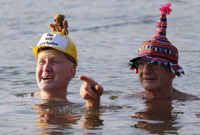 """Members of the Berliner Seehunde (Berlin Seals) ice swimmers club take a dip in Lake Orankesee during their traditional New Year swimming event in Berlin, January 1, 2015. The words on the helmet (L) reads """"The Berlin Brandenburg international airport BER is totally unsuccessful"""". (Photo by Fabrizio Bensch/Reuters)"""