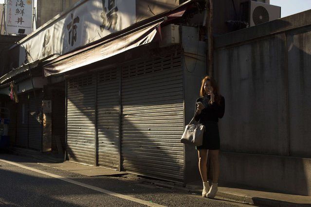 A woman stands in an alley in the outer part of the Tsukiji fish market, the Jogai Shijo, in Tokyo January 4, 2015. (Photo by Thomas Peter/Reuters)