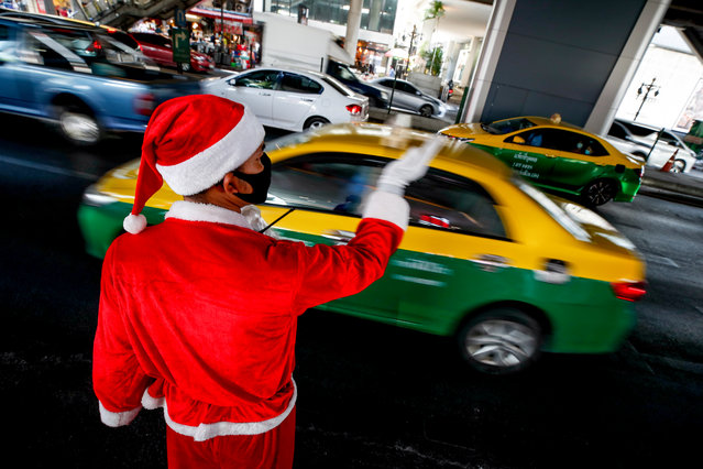 A Thai man dressed in a Santa Claus costume directs the traffic outside a shopping mall in Bangkok, Thailand, 22 December 2020. Businesses organize Christmas themed events during the festive season to attract customers and revive businesses hurt by the COVID-19 coronavirus pandemic. (Photo by Diego Azubel/EPA/EFE)