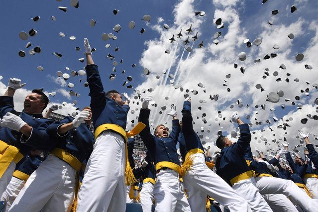 U.S. Air Force Academy cadets toss their hats in the air as the Thunderbirds fly overhead during the cadets' graduation ceremony in Colorado Springs, Colo., on Wednesday, May 23, 2018. (Photo by Jerilee Bennett/The Gazette via AP Photo)
