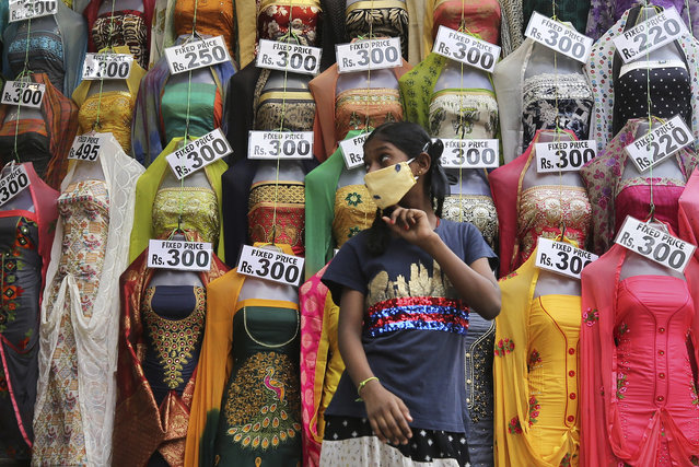 A girl wearing a face mask as a precaution against the coronavirus walks past a display of garments at a market in Bengaluru, India, Saturday, January 9, 2021. India will kick off the coronavirus vaccination drive on Jan. 16 to stem the pandemic in the world's second-most populous country. A Health Ministry statement says that priority will be given to the healthcare workers and the frontline workers, estimated around 30 million. (Photo by Aijaz Rahi/AP Photo)