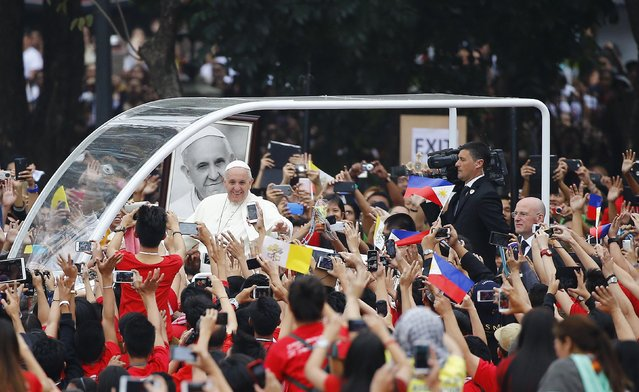 Pope Francis waves as he arrives for a meeting with young people at Manila university, January 18, 2015. The pope held morning meetings with religious leaders and young people at the university before the Mass. (Photo by Stefano Rellandini/Reuters)