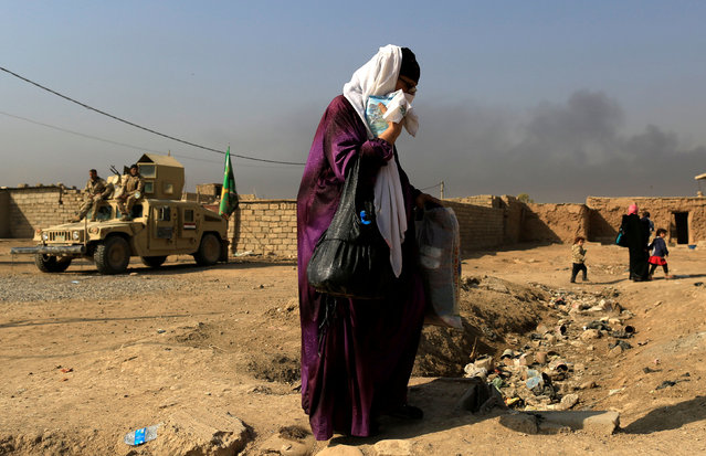 A woman who is fleeing the fighting between Islamic State and the Iraqi army in the Intisar district of eastern Mosul, walks past a military humvee while heading to safer territory in Iraq November 7, 2016. (Photo by Zohra Bensemra/Reuters)