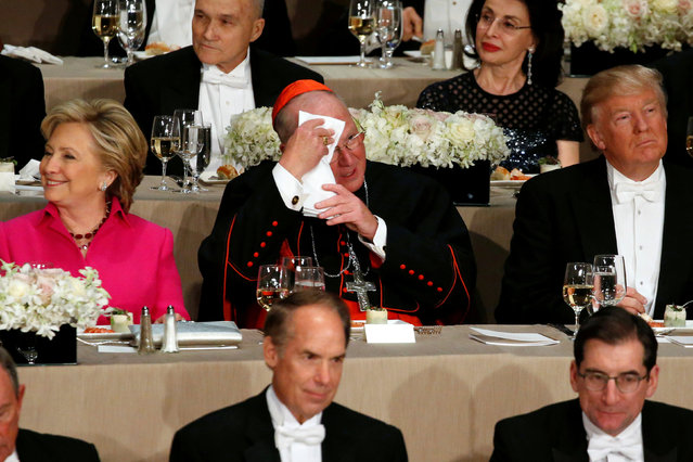 Archbishop of New York Cardinal Timothy Dolan (C) mops his brow as he takes his place between Democratic U.S. presidential nominee Hillary Clinton (L) and Republican U.S. presidential nominee Donald Trump (R) during the Alfred E. Smith Memorial Foundation dinner in New York, U.S. October 20, 2016. (Photo by Jonathan Ernst/Reuters)