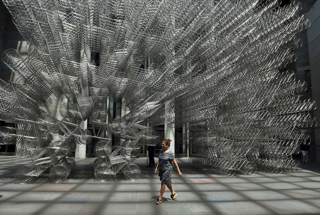 """A patron walks past """"Forever bicycles"""" by Chinese artist and human rights activist Ai Weiwei following the launch of the joint exhibition """"Andy Warhol/Ai Weiwei"""" in Melbourne on December 10, 2015. Ai Weiwei on December 10 said he believes his activism is helping to change China and the price he has paid for speaking out was worth it. (Photo by Paul Crock/AFP Photo)"""