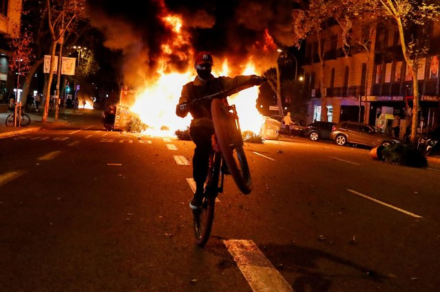 A person rides a bicycle in front of a fire during a protest against the closure of bars and gyms, amidst the coronavirus disease (COVID-19) outbreak, in Barcelona, Spain on October 30, 2020. (Photo by Nacho Doce/Reuters)