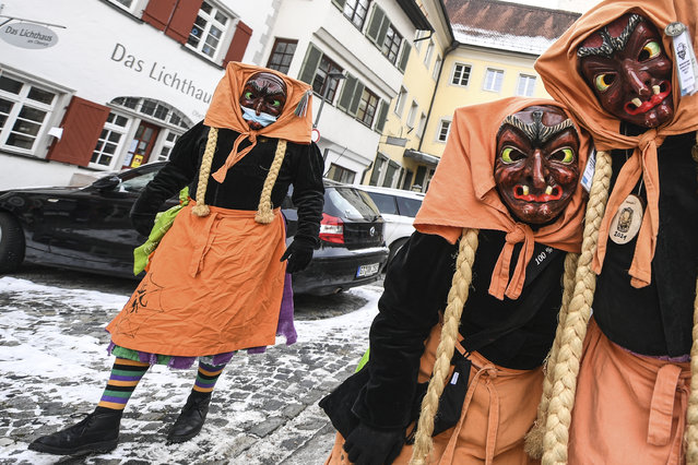 Some carnival fools of the Schwarze Veri Zunft Ravensburg walk through the Obertor gate in Ravensburg, Germany, Monday, February 15, 2021. The police broke up the gathering immediately afterwards. (Photo by Felix Kaestle/dpa via AP Photo)