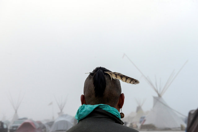 A man from the Muskogee tribe looks at the Oceti Sakowin shrouded in mist during a protest against the Dakota Access pipeline near the Standing Rock Indian Reservation near Cannon Ball, North Dakota, U.S. November 11, 2016. (Photo by Stephanie Keith/Reuters)
