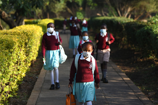 Kenyan school children wear face masks while walking to school as they resume in-class learning after a nine-month disruption caused by the COVID-19 coronavirus pandemic, in Nairobi on January 4, 2021. (Photo by Simon Maina/AFP Photo)