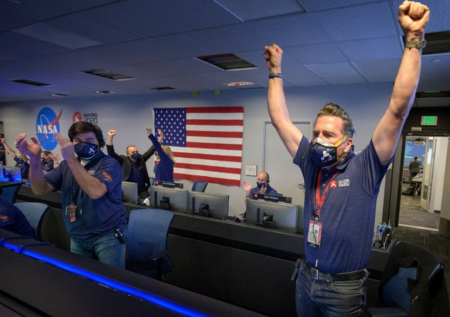 In this handout image provided by NASA, members of NASA's Perseverance rover team react in mission control after receiving confirmation the spacecraft successfully touched down on Mars on February 18, 2021 at NASA's Jet Propulsion Laboratory in Pasadena, California. A key objective for Perseverance's mission on Mars is astrobiology, including the search for signs of ancient microbial life. The rover will characterize the planet's geology and past climate, paving the way for human exploration of the Red Planet, and be the first mission to collect and cache Martian rock and regolith. (Photo by The Mega Agency)
